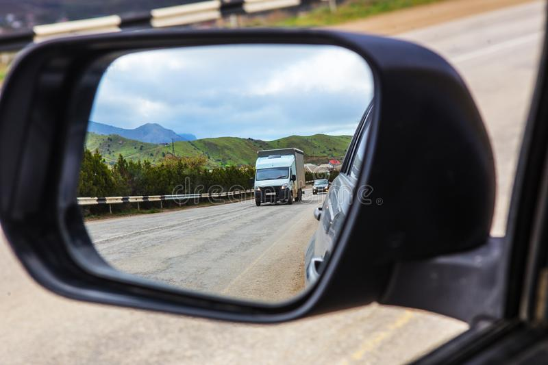 View through the rearview mirror of the car on the movement of cars on a highway. View through the rearview mirror of the car on the movement of cars on a stock images