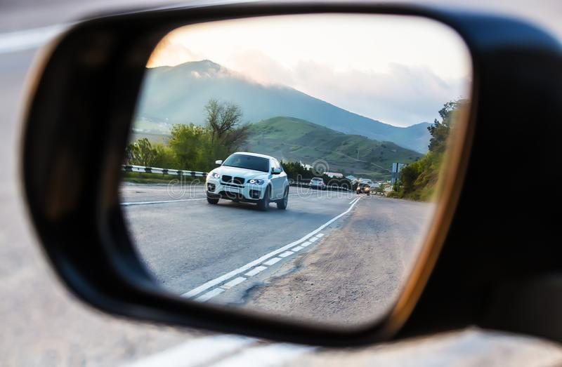 View through the rearview mirror of the car on the movement of cars on a highway. View through the rearview mirror of the car on the movement of cars on a royalty free stock image