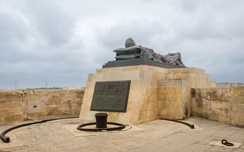 View on recumbent sculpture in the near of Siege Bell War Memorial with a description sign in Malta from the bottom royalty free stock photos