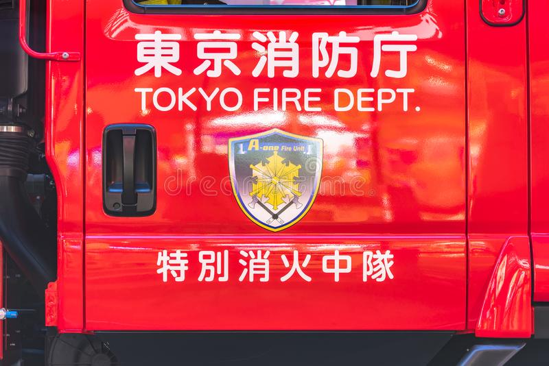 View of a red Japanese fire truck door with ideograms signifying TOKYO FIRE DEPARTMENT and firemen`s emblem with the coat of arms. Of emergency and the A-one royalty free stock photo