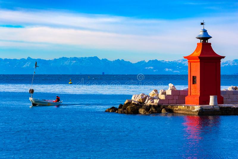 View of the red lighthouse on a pier, a fisherman on a boat and the beautiful mountain range on the horizon, Piran, Slovenia.  stock photos