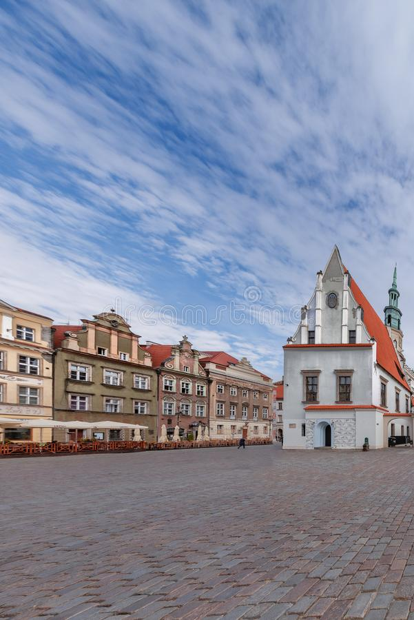 View of the red-white church and the beautifully colored houses on the central market place in Poznan Poland. The sky is blue. View of the red-white church and stock photography