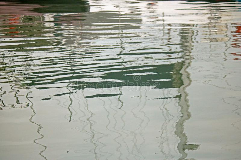 REFLECTION OF MASTS OF BOATS IN WATER royalty free stock photos