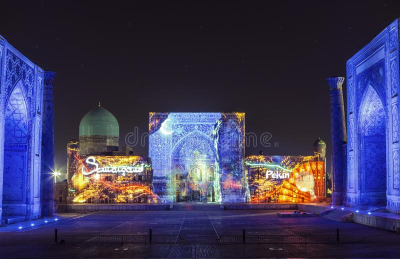 View of Registan square in Samarkand with Ulugbek madrasah, Sherdor madrasah and Tillya-Kari madrasah at night with a laser show o stock images