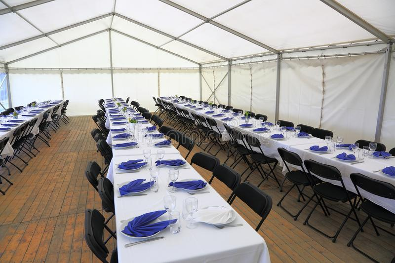 View of rented tent ready for guests. White table cloth, white plates with blue napkins and empty glass. Party celebration concept.  stock photography
