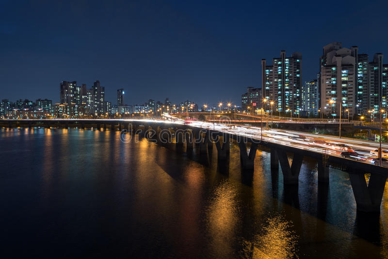 View of a residential district in Seoul at night. Lit residential district along the Han River and traffic on a bridge in Seoul, South Korea, at night royalty free stock photo