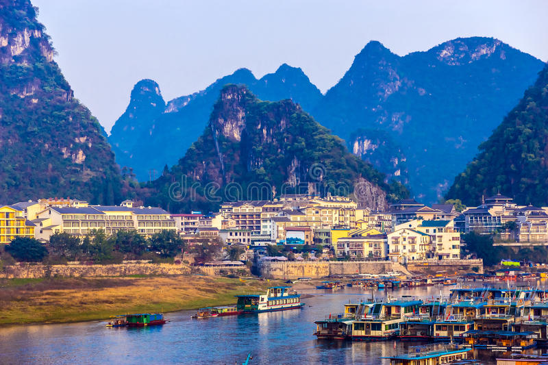 View of resort City of Guilin in Central China. With many white Buildings Boat Peer River and Karst Mountains on Background royalty free stock image