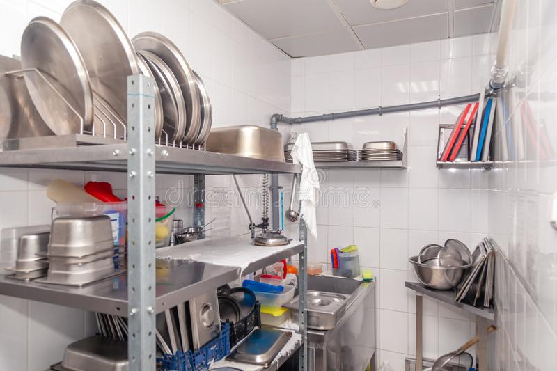 View of restaurant's professional washer, sink, brushes, metal shelving and shelves with kitchen utensils, cups, cutting board,. Bowls, lids, buckets royalty free stock image