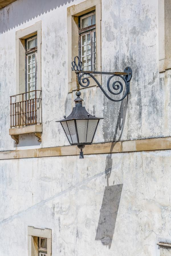 View of retro public street lamp, in street of the city of Coimbra, Portugal. Coimbra / Portugal - 04 04 2019 : View of retro public street lamp, in street of royalty free stock image