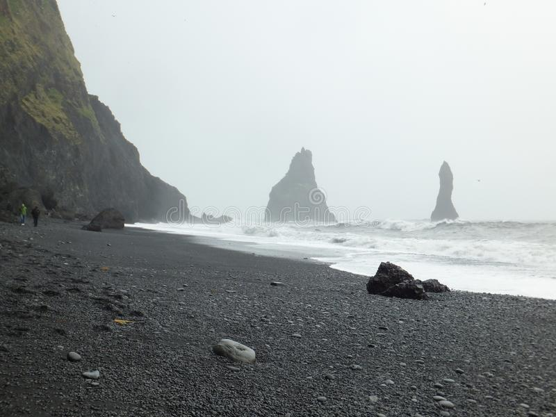 View of Reynisdrangar rock formations rising from the sea on a grey autumn day. Iceland. View of Reynisdrangar rock formations rising from the foamy sea on a royalty free stock photography