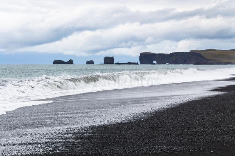 View of Reynisfjara black sand Beach and Dyrholaey. Travel to Iceland - view of Reynisfjara black sand Beach and Dyrholaey cape in Iceland, near Vik I Myrdal royalty free stock image