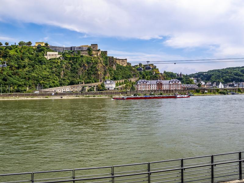 View of the Rhine River at Koblenz, Germany. View of the Rhine River with a cargo ship, Phillipsburg Palace, Ehrenbreitstein Fortress and the aerial tramway royalty free stock photos