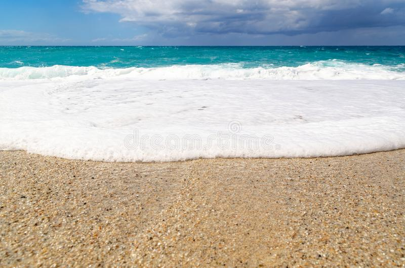 Turquoise water on the Riaci beach near Tropea, Italy. View from Riaci beach on the turquoise water waves, cloudy sky and horizon over water. This beach is stock images