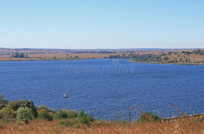 VIEW OF RIETVLEI DAM. View of a dam of water with blue colour in winter surrounded mostly by dry vegetation royalty free stock photo