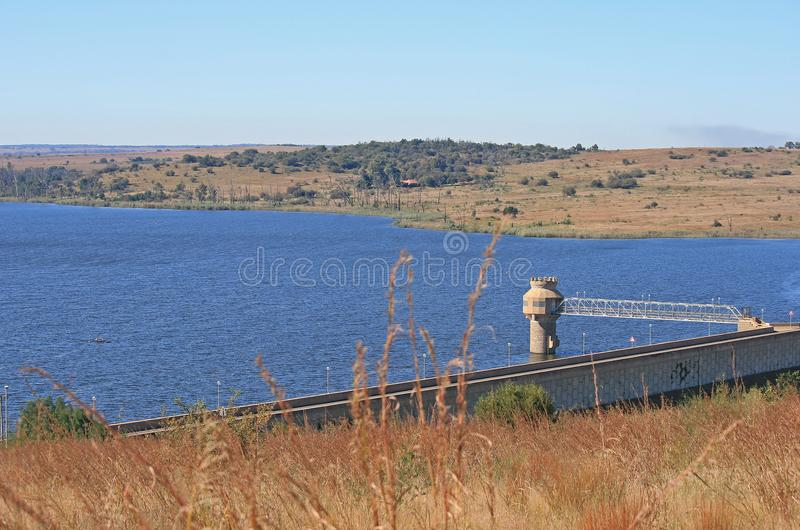 VIEW OF RIETVLEI DAM WATER SUCTION TOWER. View of a dam of water with blue colour in winter surrounded mostly by dry vegetation with water suction tower royalty free stock photo