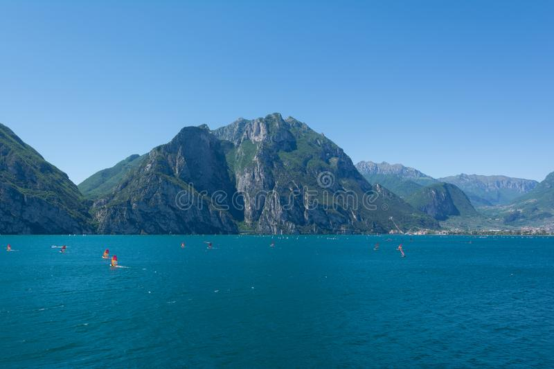 View of Riva Del Garda lakeshore with lots of windsurfers on the foreground, Italy. View of Riva Del Garda lakeshore with lots of windsurfers on the foreground stock photography