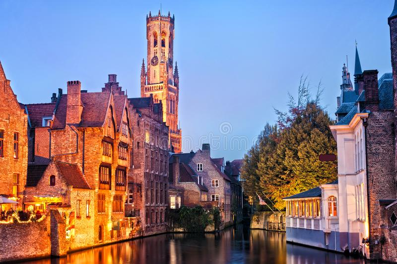 View of river canal and Belfort tower at twilight from Rozenhoedkaai,famous boat tour point in Bruges, Belgium. View of river canal and Belfort Belfry tower at royalty free stock photos