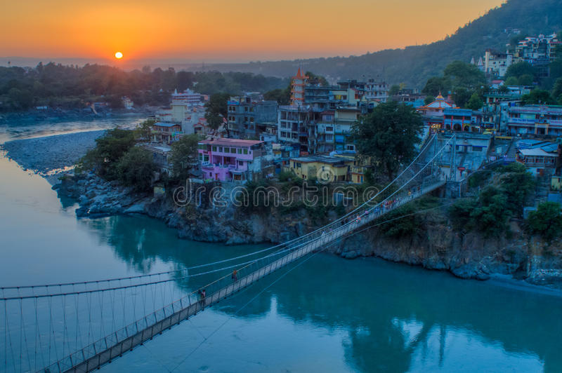 View of River Ganga and Lakshman Jhula bridge at sunset. Rishikesh. India. View of River Ganga and Ram Jhula bridge at sunset with a blue sky and colorful houses royalty free stock image