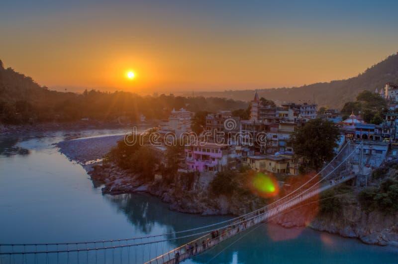 View of River Ganga and Lakshman Jhula bridge at sunset. Rishikesh. India stock photography