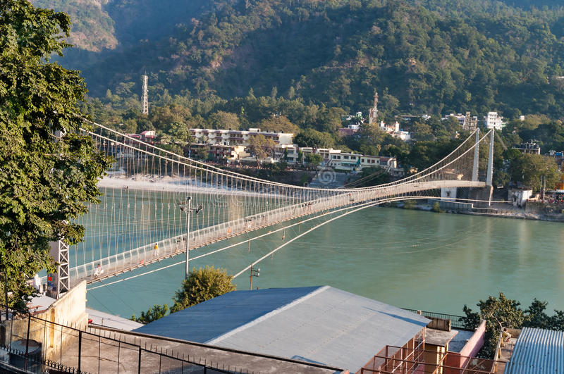 View of River Ganga and Ram Jhula bridge. RISHIKESH, INDIA - DEC 11, 2014: View of River Ganga and Ram Jhula bridge. Rishikesh is World Capital of Yoga, has royalty free stock photography