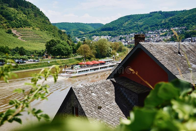 View of the river Mosel with tourist ship, green hills with vineyard and houses of small village. Germany, Europe stock image