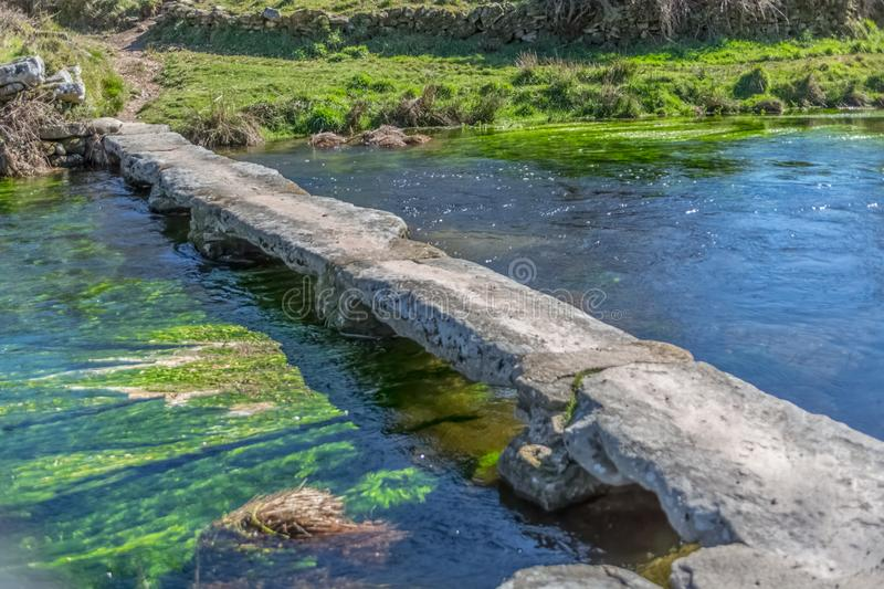 View of a river, with old and archaic stone bridge for pedestrian passage. Trees, rocks and vegetation on the banks, reflections in the water and bright colors royalty free stock image