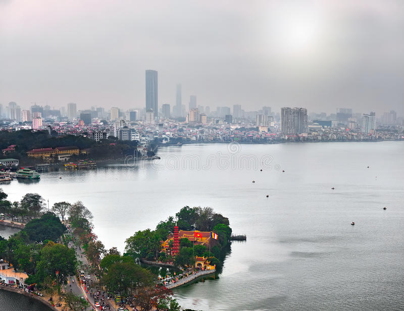View of the River Red River and the bridge across it (Hanoi, Vietnam) against the background of skyscrapers and sun that shines th. Rough the mist on a cloudy stock photos