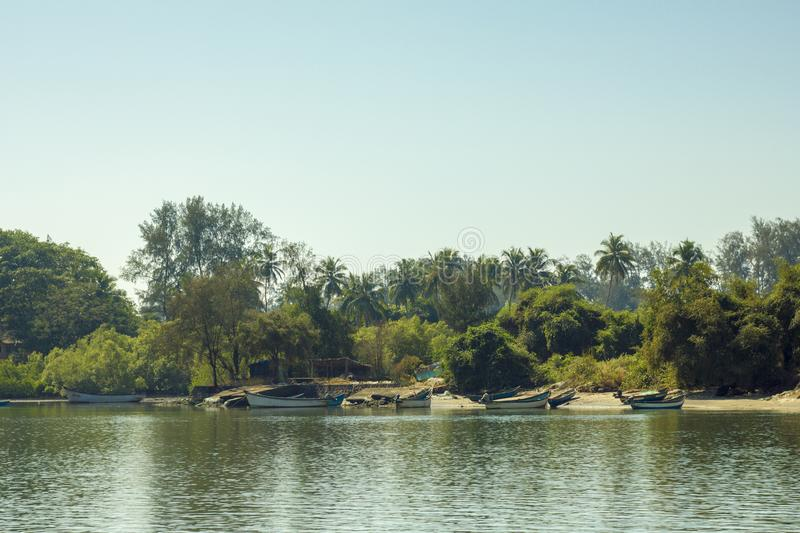 A view from the river to the sandy shore with boats against the green jungle under a clear blue sky royalty free stock images