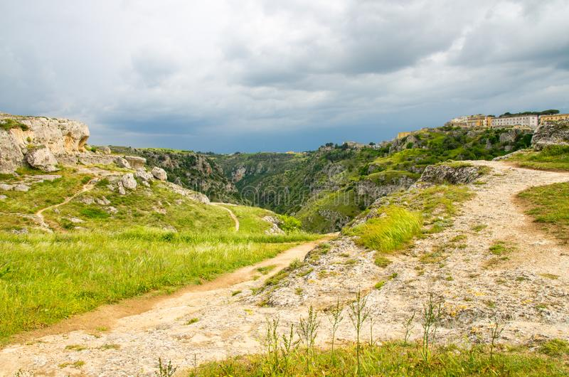 View of canyon with rocks and caves Murgia Timone, Matera Sassi,. View of river valley with ravine canyon, rocks, green grass, path, caves di Murgia Timone and stock photo