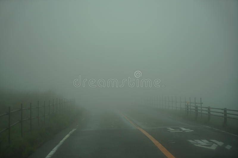 View of roadway and fence full of white fog while driving through local road on rainy and bad weather day on mount Aso area. Kumamoto, Japan royalty free stock photos