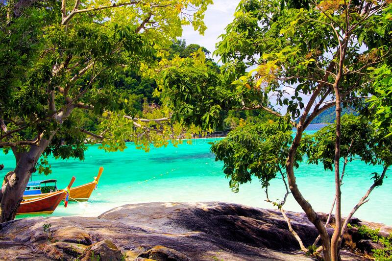 View from rock beyond green trees of small lonely remote island on turquoise water with thai long-tail boats, Ko Lipe, Thailand. View from rock beyond green stock images