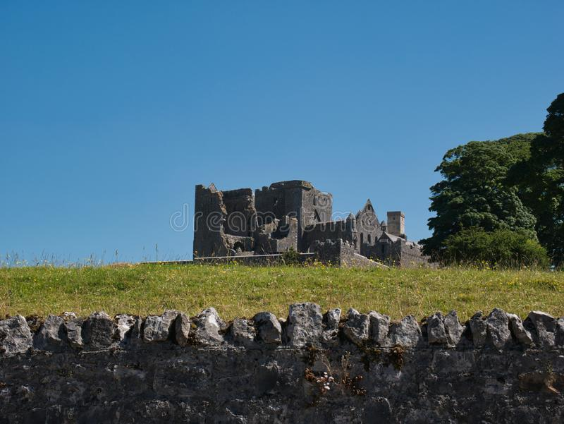 Rock of Cashel with a stone wall in the foreground royalty free stock photo