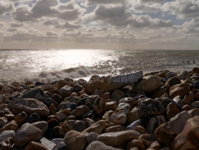View of a rocky beach at sunset. Breaking wave, beautiful reflection on the sea, horizon and clouds are seen royalty free stock photos