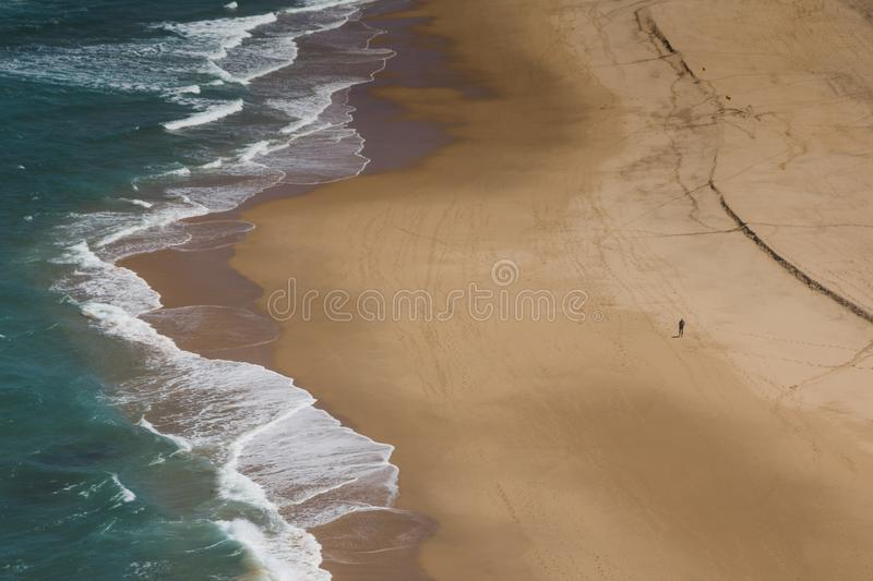 View of rocky coast of the Atlantic Ocean and beach with large waves.Tourist is walking along the beach.Praia Grande. Sintra. Port stock image