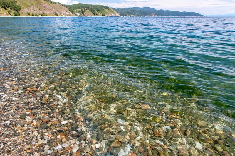 View of the rocky coast with clear transparent water near the shore of Lake Baikal royalty free stock photos