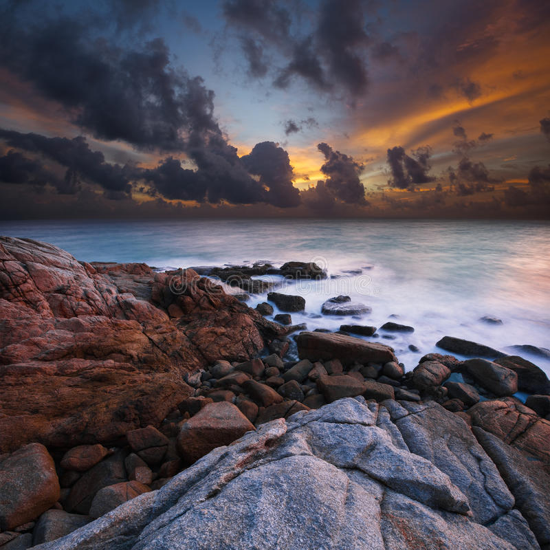 View of a rocky coast at sunset stock photos