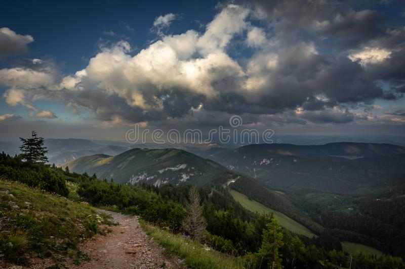 View on rocky path through grassy rax plateau in the cloudy sunset. View on rocky path on hike Dambocksteig from Schneeberg, highest peak Kosterwappen, along royalty free stock images