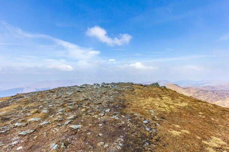 A view from a rocky summit plateau over a valley under a majestic blue sky and white clouds.  stock images