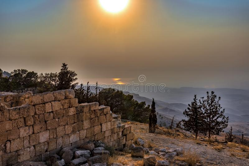 View of a rolling mountain landscape with trees and fog at sunset, called Mount Nebo in Jordan, where the Bible, God showed Moses stock photos
