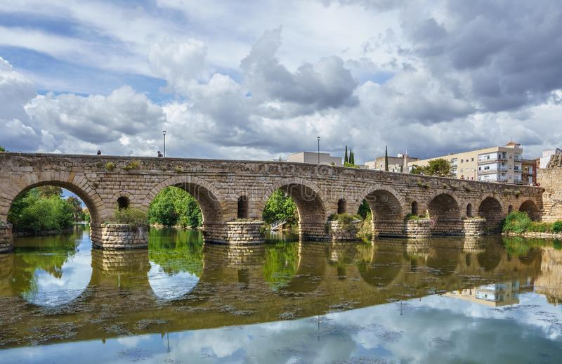 View of the Roman bridge of Merida with its reflection on the Guadiana river. royalty free stock photos