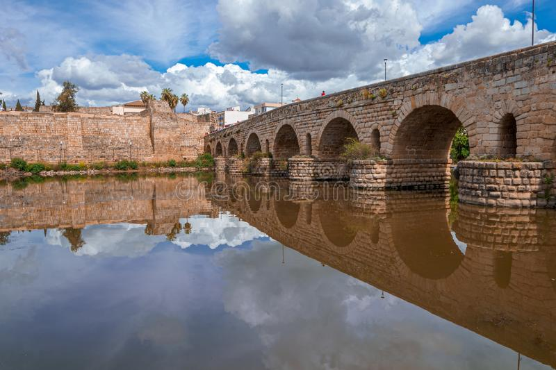 View of the Roman bridge of Merida with its reflection on the Guadiana river. stock image