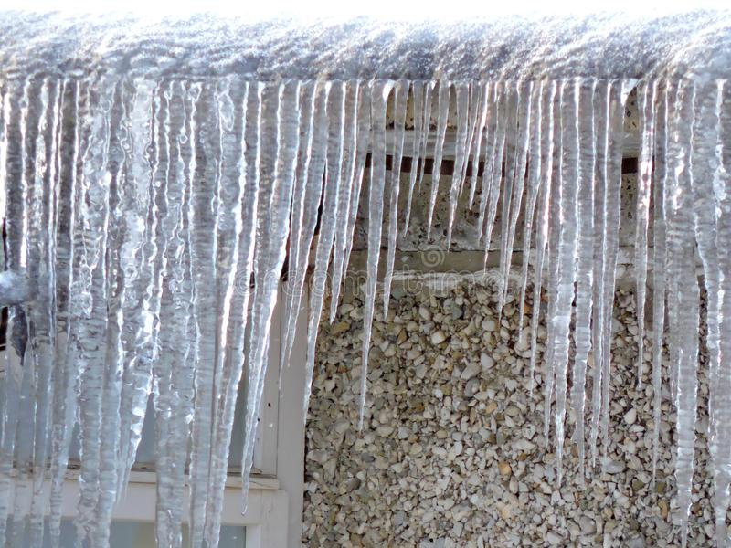 White snow  and icicles on the roof of stone house in winter royalty free stock images