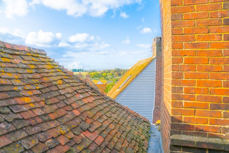 View between roof tops and brick walls to English Landscape. From The Tea House B & B in Rye United Kingdom stock image