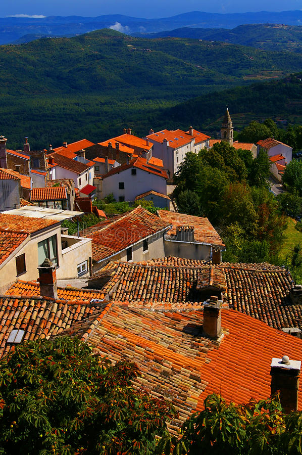 View of Rooftops and Hills from Motovun Croatia. Tile rooftops, church steeple and vineyards viewed from Motovun Croatia. This image has all technology items royalty free stock images