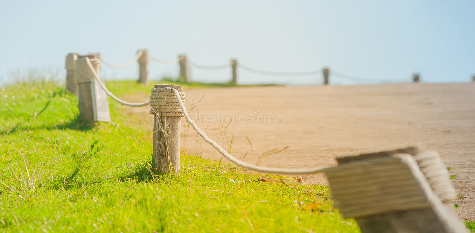 View of rope tired around wooden pole or pillar of fence beside road at countryside. stock images