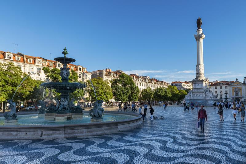 View of the Rossio Square with tourists walking by, in the pombaline downtown of the city of Lisbon royalty free stock image