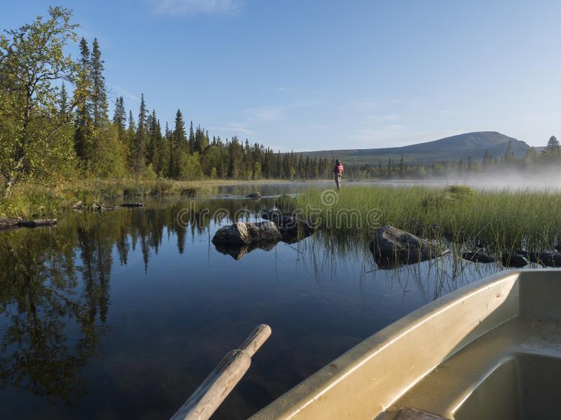 View from rowing boat on Fisherman man at lake Sjabatjakjaure in Beautiful sunny morning haze mist in Sweden Lapland nature. Mountains, birch trees, spruce royalty free stock photography