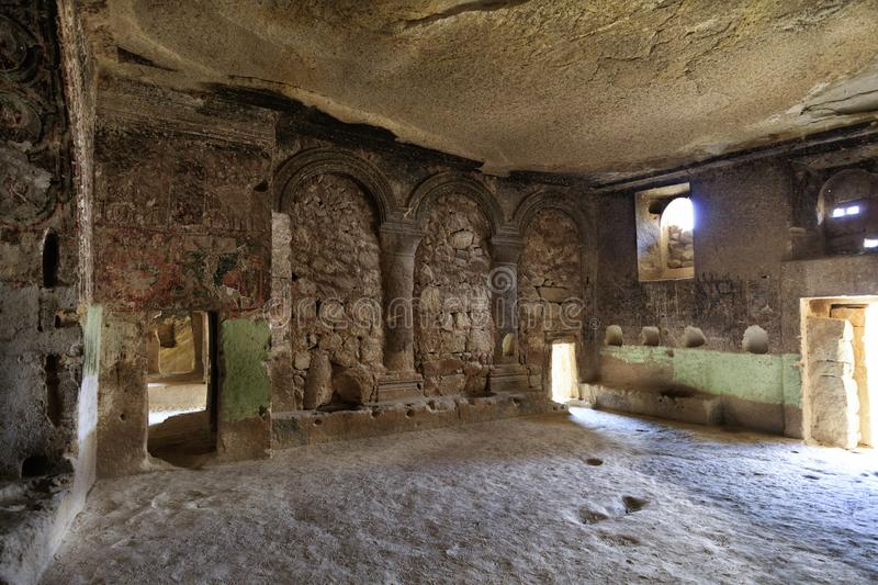 View of the ruins of a large hall of the underground ancient temple of a church in Cappadocia. Ancient frescoes on the ruins of the stone walls of an antique royalty free stock photography