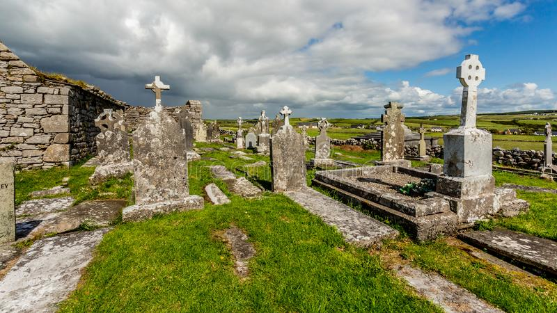 View of the ruins of the medieval church of Killilagh and the graveyard in the village of Doolin stock images