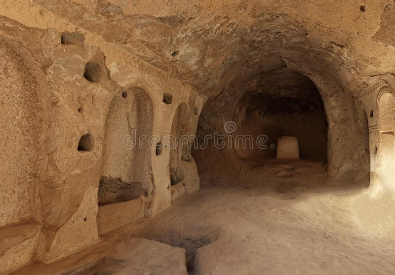 View of the ruins of the premises of the ancient prayer room in the caves of the old sandstones in the valleys of Cappadocia. Old frescoes on the ruins of the royalty free stock images